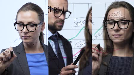 vzorec : 3 in 1 video. Man and woman draws various growth charts, calculating prospects for success in a modern glass office. Vertical video montage. Dostupné videozáznamy