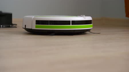 recharging : Vacuum cleaner robot that cleans a wooden floor Stock Footage