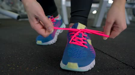 бегун трусцой : Running shoes - woman tying shoe laces in the gym Стоковые видеозаписи