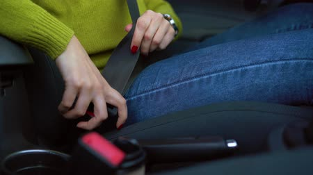 přezka : Female hand fastening car safety seat belt while sitting inside of vehicle before driving Dostupné videozáznamy