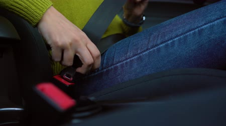 spona : Female hand fastening car safety seat belt while sitting inside of vehicle before driving Dostupné videozáznamy