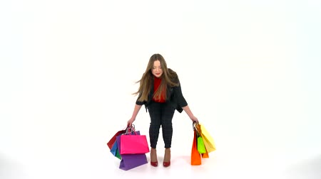 alku : Female shopper holding multicolored shopping bags on white background in studio. Lets go shopping concept