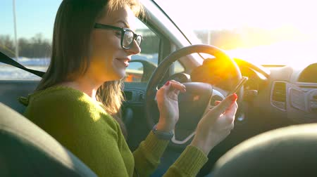 riskli : Woman in glasses using a smartphone and talking to someone in the car Stok Video