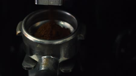 italian speciality : Process of grinding coffee beans in a coffee machine closeup