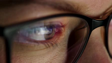 looking distance : Woman in glasses looking on the monitor and surfing Internet. The monitor screen is reflected in the glasses Stock Footage