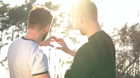 gays : Young gay couple making heart symbol with their hands at sunset outdoors