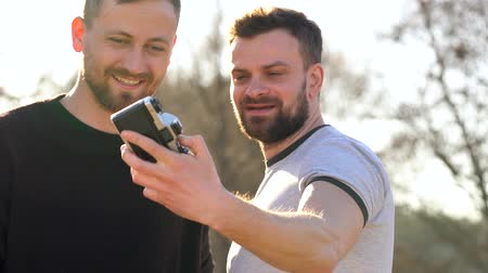 candid laughter : Young gay couple taking photo of themself on a film camera in the spring evening. Slow motion