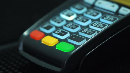register : Shop assistant inserting a credit card into a pos and inserting pin-code of the card