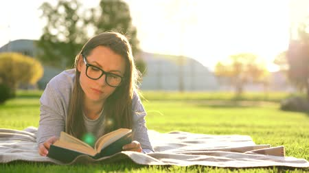novel : Girl in glasses reading book lying down on a blanket in the park at sunset