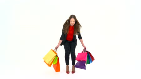 barganha : Female shopper holding multicolored shopping bags on white background in studio. Lets go shopping concept