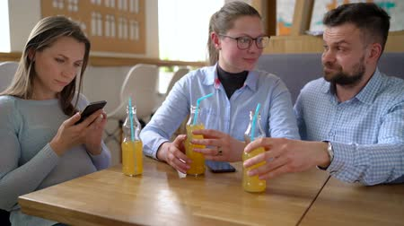 dialog : Three friends sit in a cafe, drink juice and have fun communicating