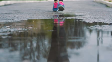 кроссовки : Close up shot of legs of a runner in sneakers. Female sports man jogging outdoors in a park, stepping into muddy puddle.