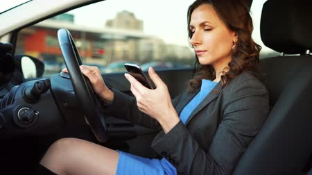 riskli : Woman in a blue dress and jacket using a smartphone in the car