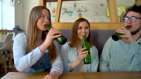limonada : Three friends sit in a cafe, drink water or beer and have fun communicating. Slow motion