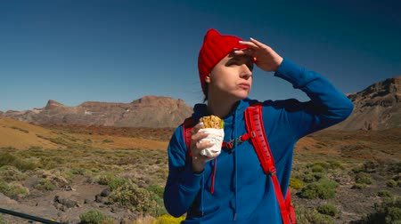 kanarya : Hiking woman eating sandwich after hike on Teide, Tenerife. Caucasian female tourist on Tenerife, Canary Islands Stok Video
