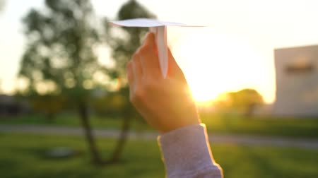 paper airplane : Hand launches paper airplane against sunset background. Slow motion Stock Footage