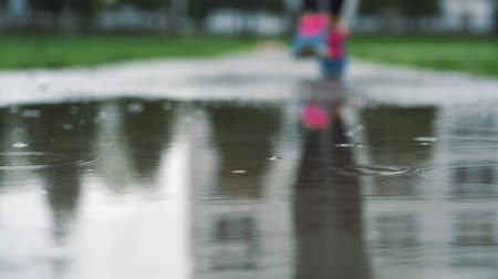 bruk : Close up shot in different speed of legs of a runner in sneakers. Female sports man jogging outdoors in a park, stepping into muddy puddle.