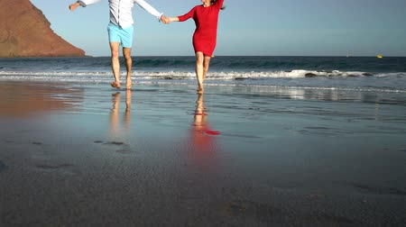 блаженство : Couple in love carefree running from the water and waving their hands to someone on the beach. Picturesque ocean coast of Tenerife, Canarian Islands
