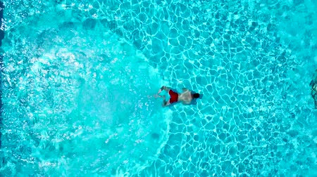 drone : View from the top as a man dives into the pool and swims under the water Stock Footage