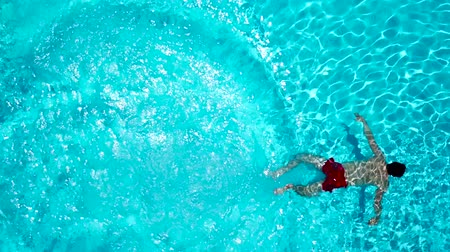 yüzme havuzu : View from the top as a man dives into the pool and swims under the water Stok Video