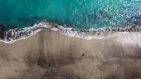 pegada : Top view of a woman in red dress walking barefoot along wet sand ocean beach