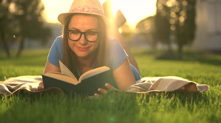 lefekvés : Girl in glasses reading book lying down on a blanket in the park at sunset