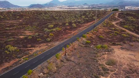 work at height : Aerial view of motorcyclist traveling up a desert road Stock Footage