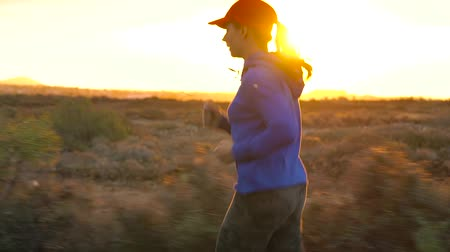závodní dráha : Woman runs along the deserted asphalt road at sunset, back view. Mountains on the background. Slow motion