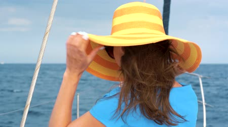 enjoys : Woman in a yellow hat and blue dress waving hair and smiling on yacht on summer season at ocean. Slow motion