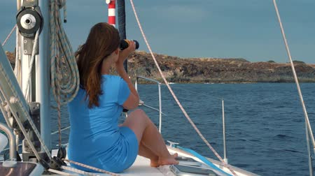 enjoys : Womanin a blue dress sits aboard the yacht and exploring the horizon through binoculars. Slow motion