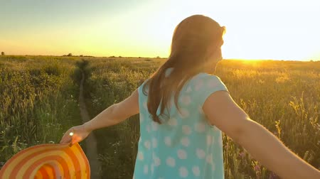 ведущий : Follow me - happy young woman in yellow hat pulling guys hand. Hand in hand walking throw a field of green wheat at sunset. Slow motion