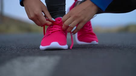 koronka : Running shoes - woman tying shoe laces on a desert road in a mountainous area. Slow motion