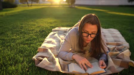 клетчатый : Girl in glasses reading book lying down on a blanket in the park at sunset