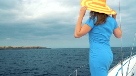 enjoys : Woman in a yellow hat and blue dress girl rests aboard a yacht on summer season at ocean
