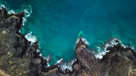 tyrkysový : Top view of a deserted coast. Rocky shore of the island of Tenerife. Aerial drone footage of sea waves reaching shore