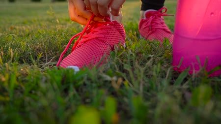 бегун трусцой : Running shoes - woman tying shoe laces. Slow motion
