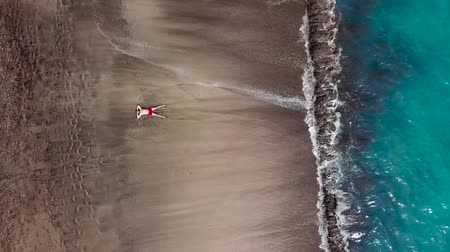 tyrkysový : Aerial view of a man in red shorts lies on deserted black volcanic beach in a star pose. Aerial drone footage of sea waves reaching shore