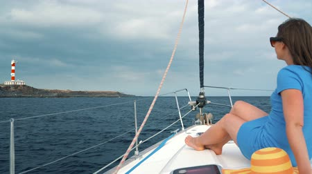 latarnia morska : Woman in a yellow hat and blue dress girl rests aboard a yacht near the lighthouse on summer season at ocean Wideo