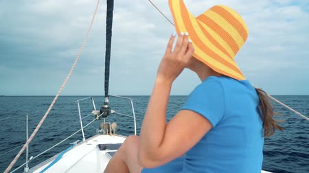 sailing boat : Woman in a yellow hat and blue dress girl rests aboard a yacht near the lighthouse on summer season at ocean. Slow motion Stock Footage