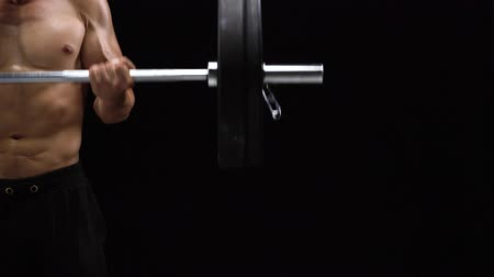 žíly : Man is doing exercises with a barbell, training on a black background in the studio. Half body in frame