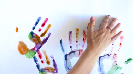 muž : Creative concept - man and woman make prints of their painted hands on a white background