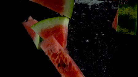 Pieces of watermelon fall and float in water, black background