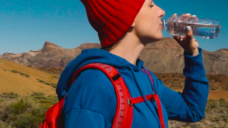 Hiking woman drinking water after hike on Teide, Tenerife. Caucasian female tourist on Tenerife, Canary Islands