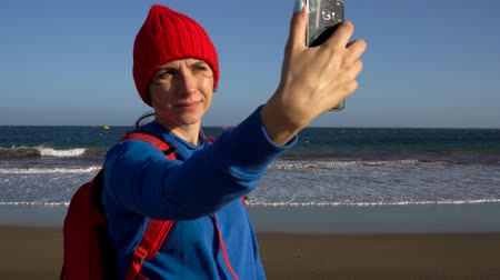 屋外で : Active hiker woman walks on the beach and makes self photo on her smartphone. Caucasian young woman with backpack on Tenerife, Canary Islands, Spain