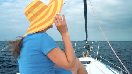 Woman in a yellow hat and blue dress rests aboard a yacht near the lighthouse on summer season at ocean. Slow motion