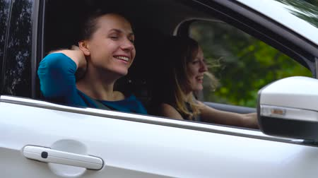 Two young women ride in a car and have fun