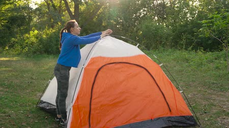 turisták : Woman is putting a tourist tent in the forest