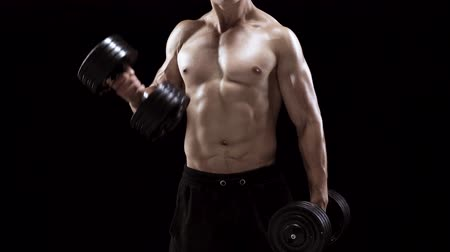 Man flexes his hands with dumbbells, training his biceps on a black background in the studio Stock Footage