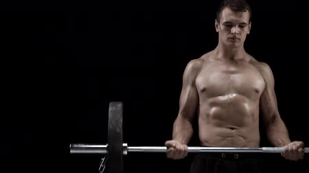 muž : Man is doing exercises with a barbell, training on a black background in the studio
