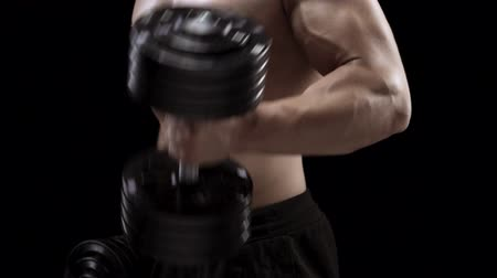 Man flexes his hands with dumbbells, training his biceps on a black background in the studio, side view Stock Footage